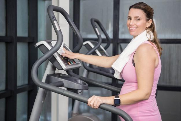 kvinde på crosstrainer maskine